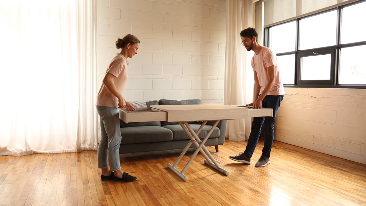 Man and woman extending a transforming table with built-in extensions