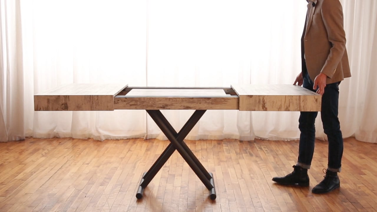 Man closing a table with built in extensions